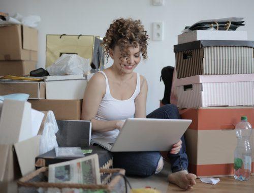 jeune femme assise au milieu de cartons de déménagement